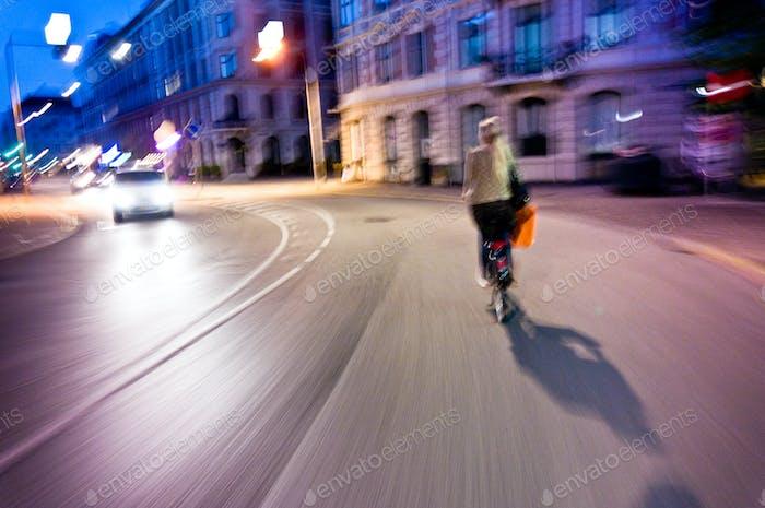 Frau fährt Fahrrad in der Nacht - echte Bewegungsunschärfe und lebendige Farben
