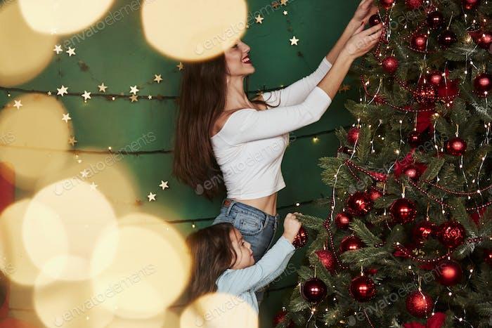 Мама и дочь украшают елку. Зеленый фон