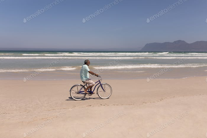Side view of senior man riding bicycle on beach in the sunshine with mountains in the background