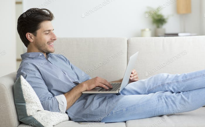 Guy Working On Laptop Computer Lying On Sofa At Home