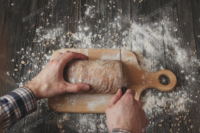 man in plaid shirt with knife cut home-baked bread on wooden board