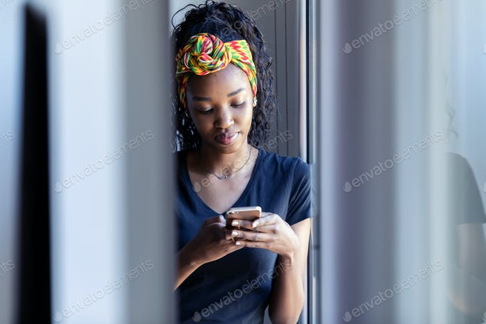Pretty young woman using her mobile phone while standing next to the window at home.