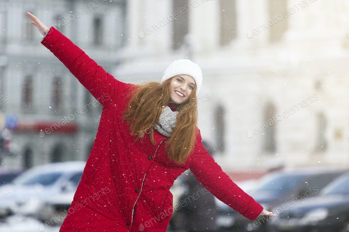 Positive young girl having fun on winter street