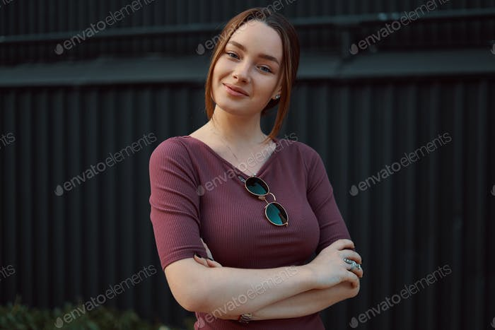 Portrait of attractive young woman posing against dark wall
