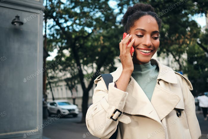 Smiling African American girl in stylish trench coat joyfully talking on cellphone on city street