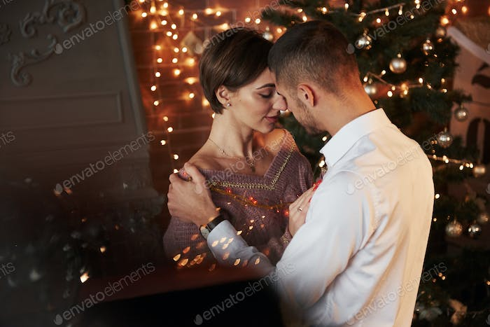 Closeness of the guy and girl in luxury wear that dancing and flirting