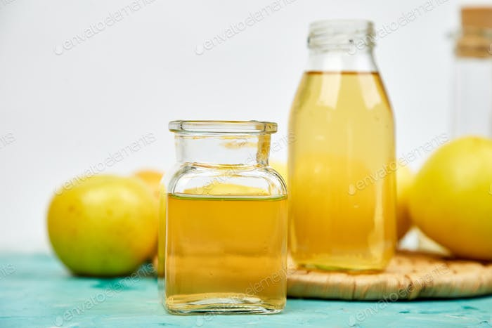 Botella de vidrio de vinagre orgánico de manzana sobre Fondo azul.
