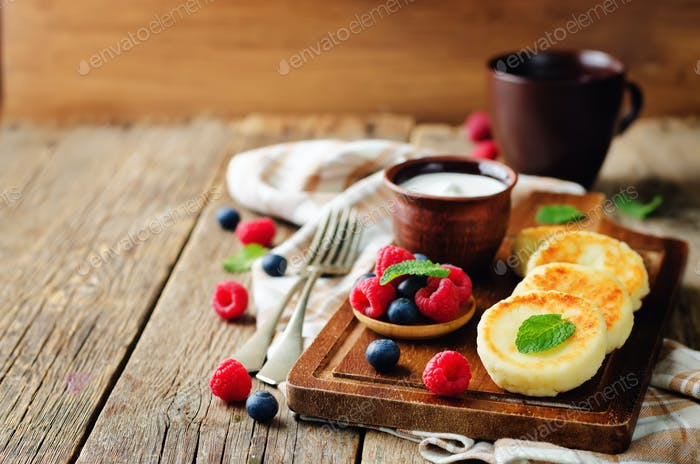Cottage cheese pancakes with honey, sour cream and berries