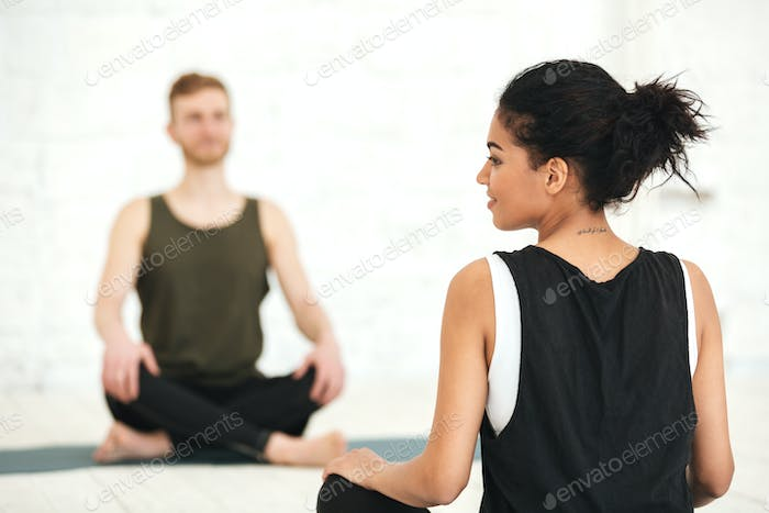 Young woman having a yoga class with male instructor