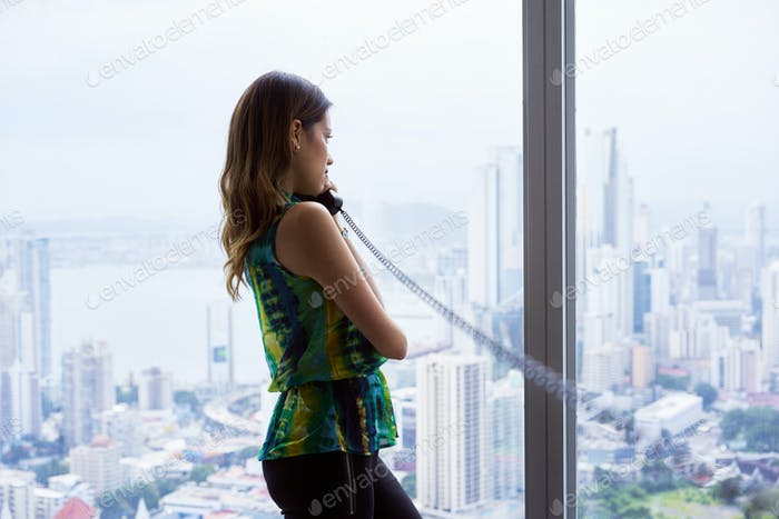 Woman Talking With Wired Telephone In Office Looking Outside Win