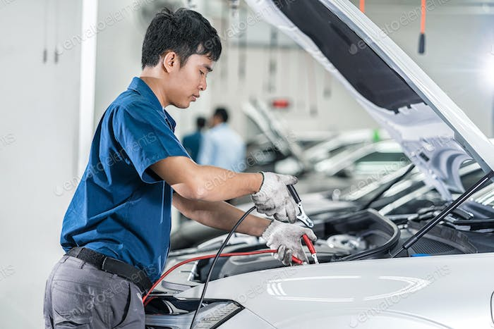 Asian mechanic Checking and repairing the car in maintainance service center