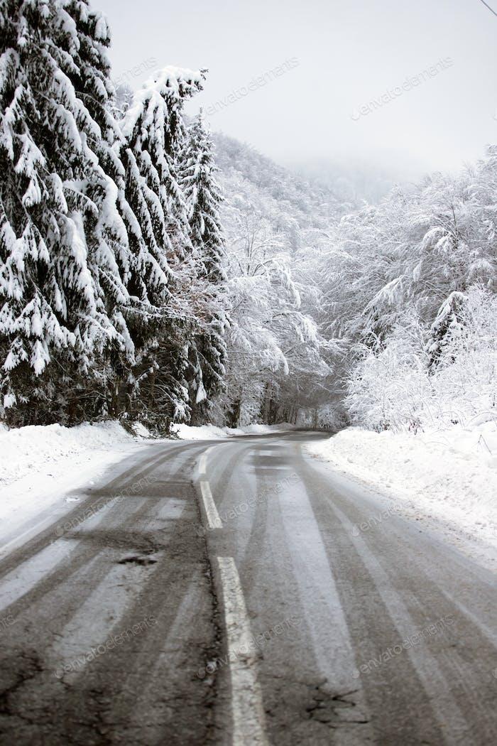 Leere Straße mit Schneebänken an den Seiten.