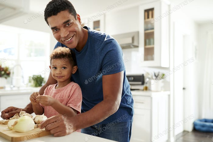 Man standing at kitchen worktop preparing food with his toddler son looking to camera