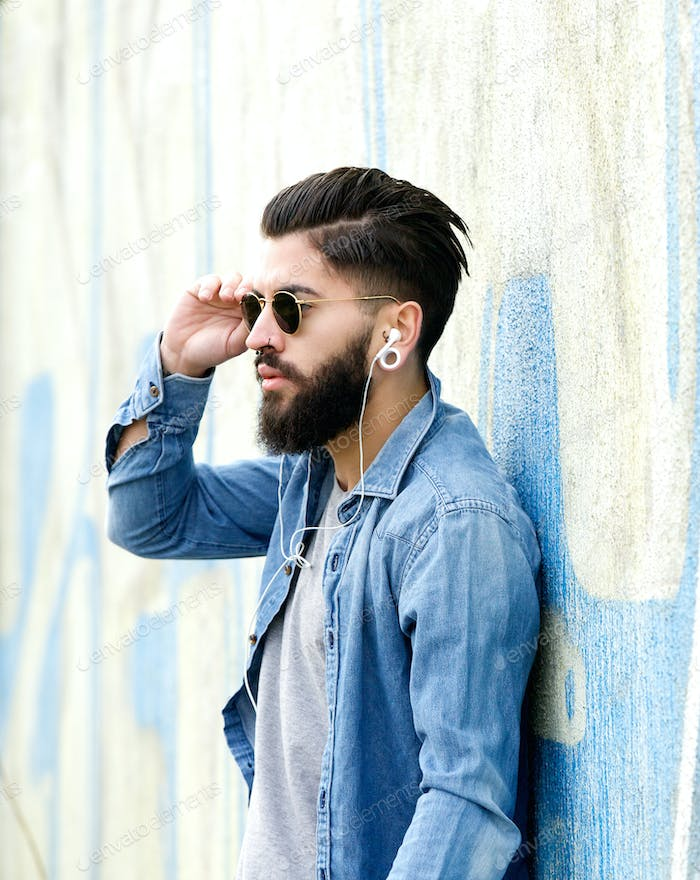Handsome man with beard listening to music with earphones
