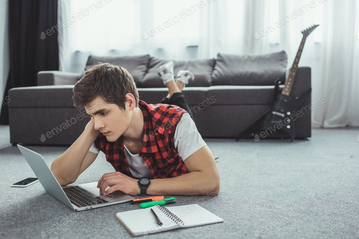 male teenager studying with copybook and laptop while lying on floor