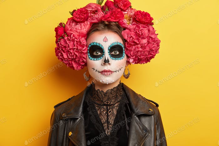 Day of Dead concept. Young woman has funky makeup and costume, wears wreath of red flowers, has trad