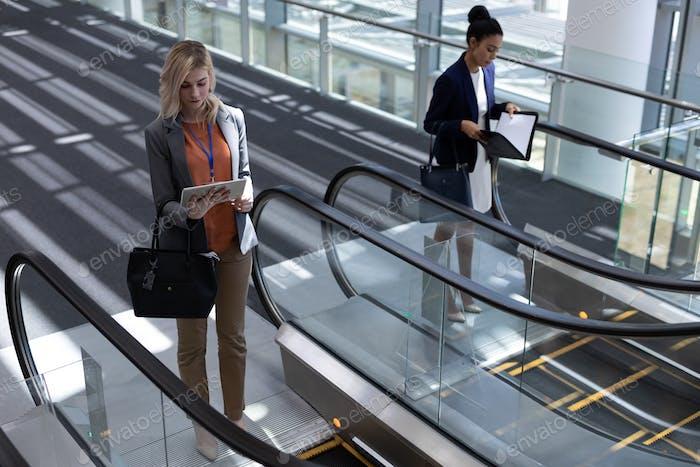 Vorderansicht der jungen multiethnischen Geschäftsfrauen mit Rolltreppe im modernen Büro