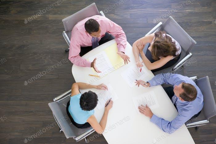 Четыре бизнесмена за столом заседаний
