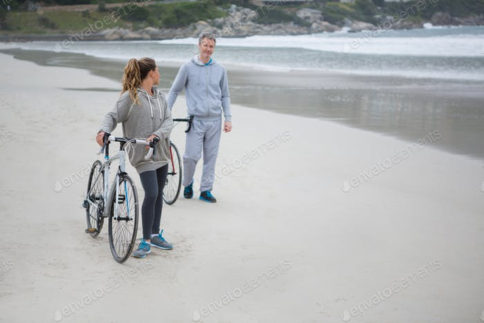 Couple with bicycle interacting with each other on beach