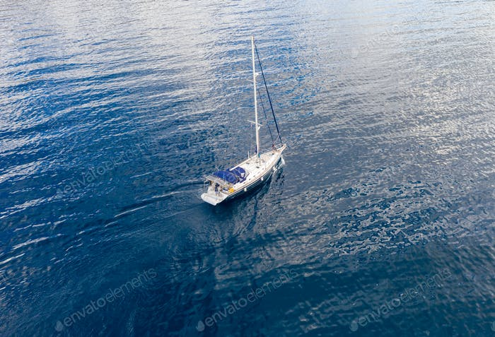 Sailing boat on calm sea background, aerial drone view