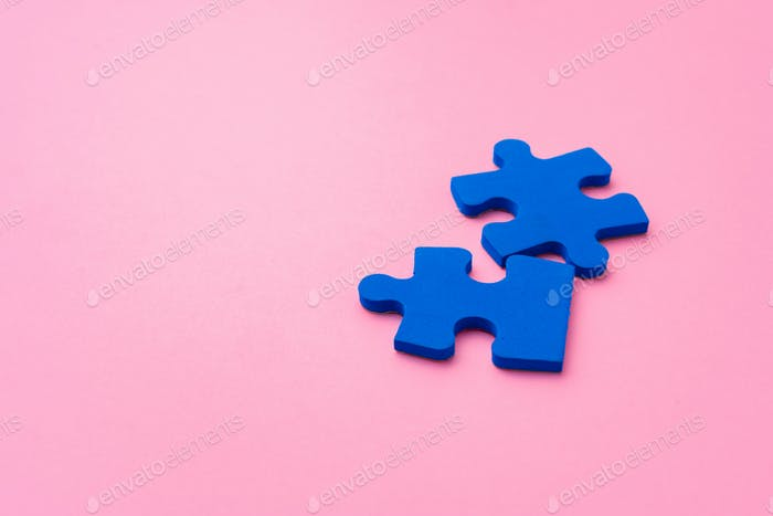 Blue puzzle pieces on paper background top view
