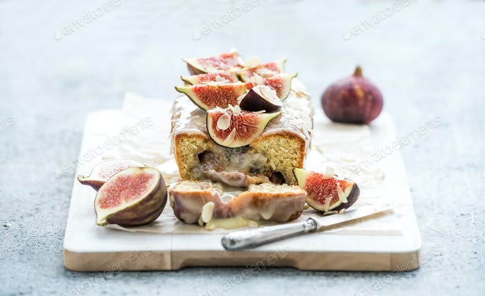 Loaf cake with figs, almond and white chocolate on wooden serving board