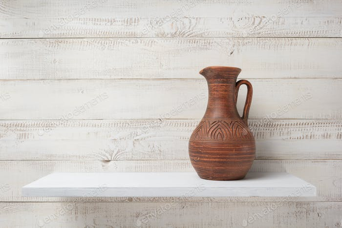 clay jug at shelf on white wooden background
