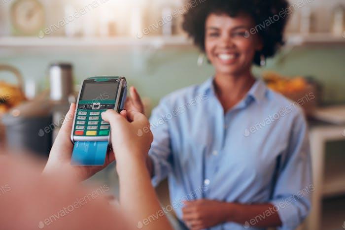 Weibliche Kunden, die mit Kreditkarte an der Saftbar bezahlen