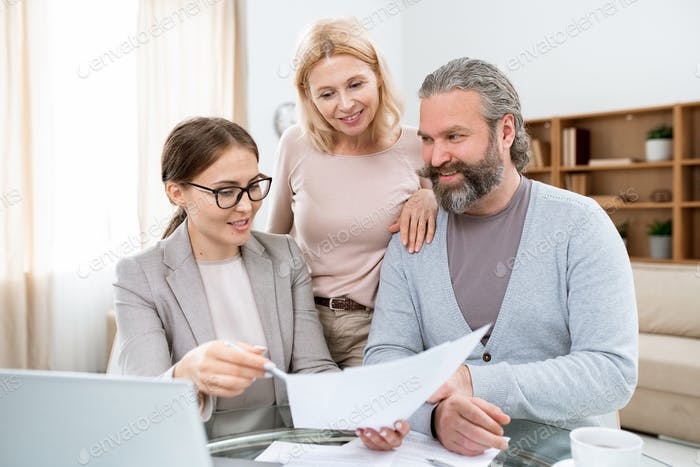 Happy mature spouses listening to real estate or insurance agent explanations