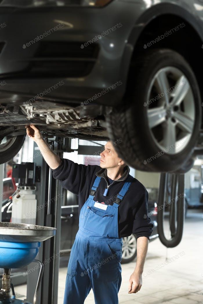 Mechanic in uniform is working in auto service
