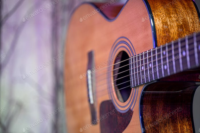 Acoustic guitar on a beautiful colored background. The concept of stringed instruments.