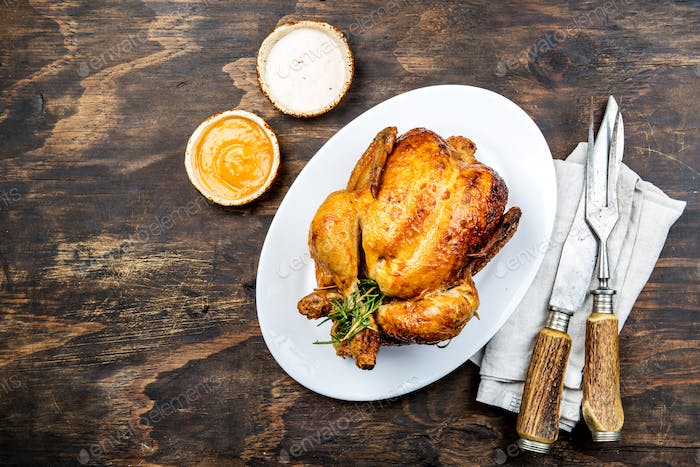 Roasted Chicken with Rosemary Served on White Plate with sauces on Wooden table, top view