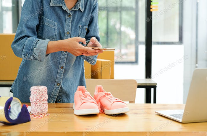 Online sellers use mobile phone to take pictures of shoes sent to customers.