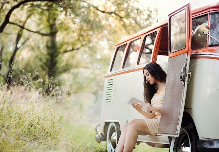 Ein junges Mädchen mit einem Buch mit einem Auto auf einer Roadtrip durch die Landschaft, Lesen.