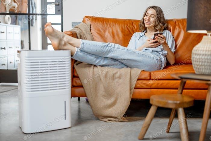 Woman sitting near air purifier and moisturizer appliance