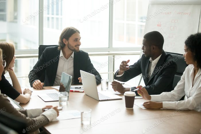 Business executives discussing project ideas at team meeting conference table
