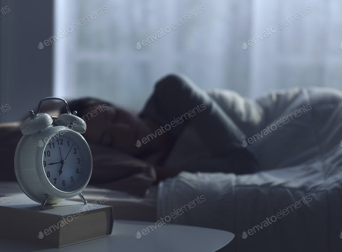 Woman sleeping in her bed and alarm clock