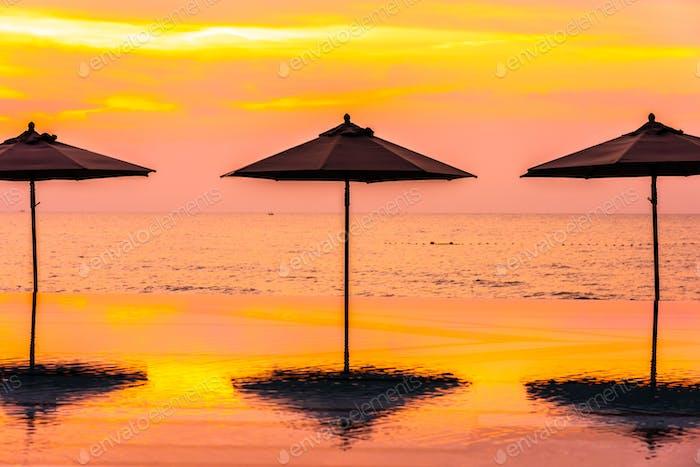Sonnenschirm und Stuhl rund um Schwimmbad neary Meer Meer Meer Strand in