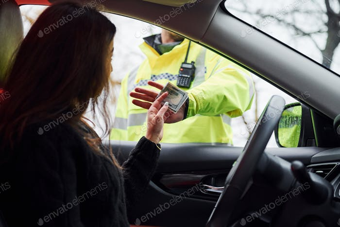 Male police officer in green uniform refuse to take bribe from woman in vehicle