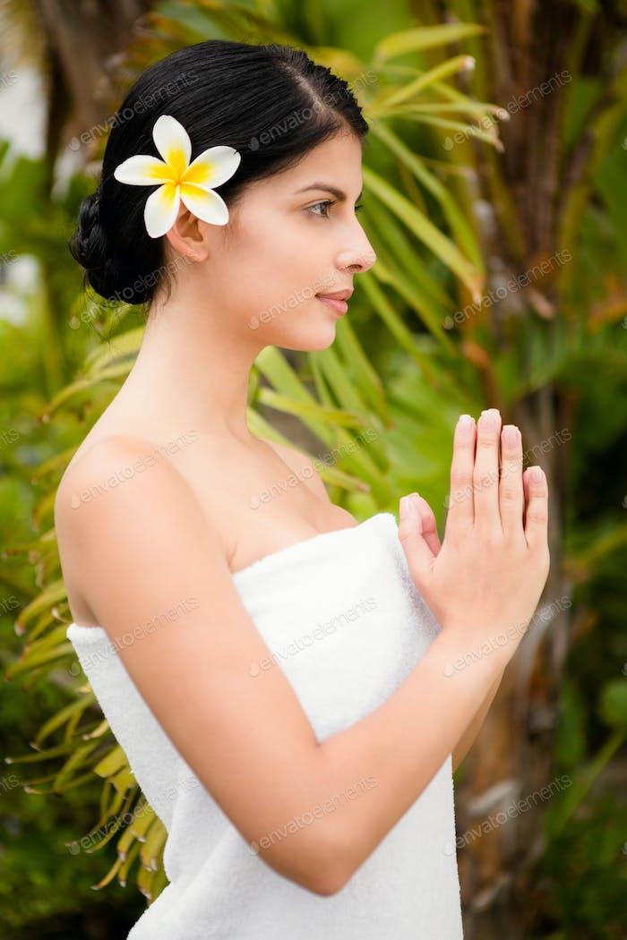 Hübsche Frau betet vor ihrem Wellness-Tag in einer Gesundheitsfarm