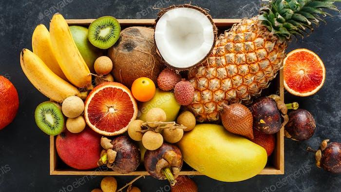 Fresh exotic fruit in a box. Golden pineapple, blood orange, coconut, mini bananas, longan