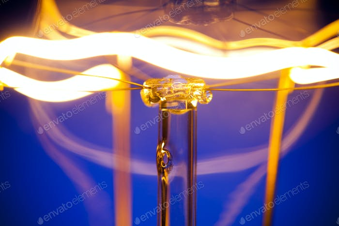 Close-up of burning light bulb with tungsten filament in center