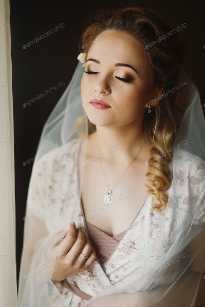 Schöne Braut Blick aus dem Fenster, Morgen Hochzeit Vorbereitung