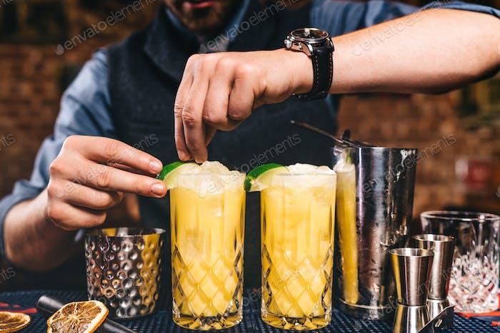 Barmann garniert und bereitet ausgefallene Cocktails. Orangencocktails auf Wodka-Basis an der Bar