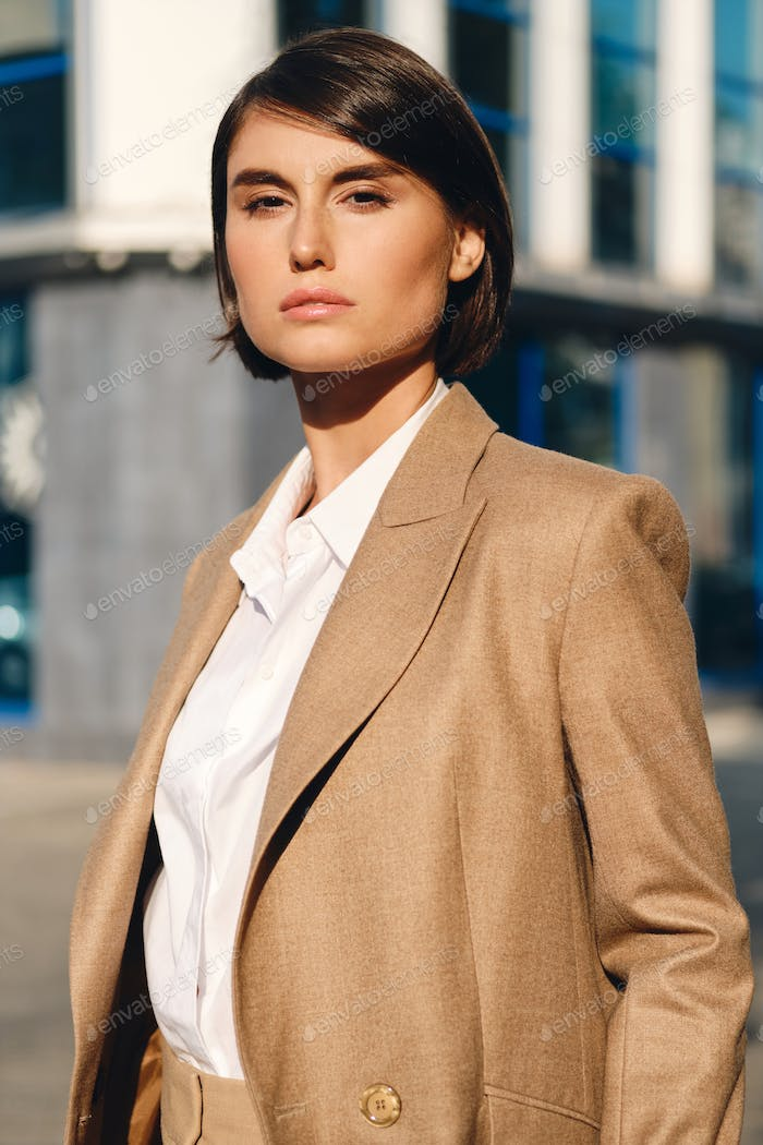 Young attractive stylish businesswoman in suit intently looking in camera on street
