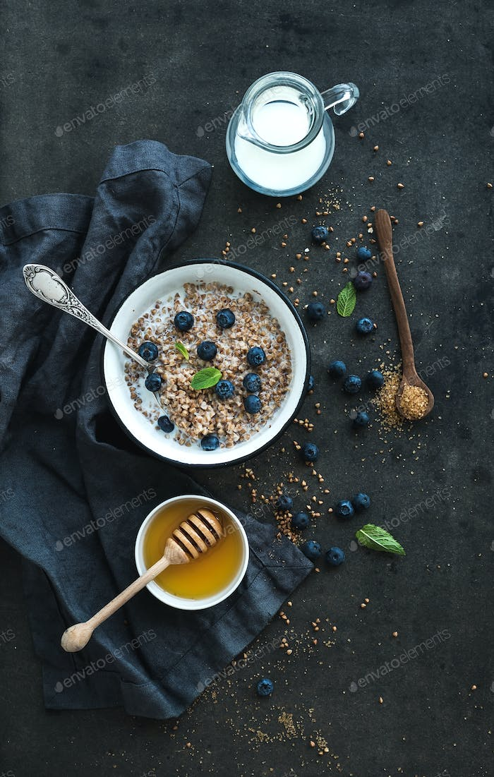 Rustic healthy breakfast set. Cooked buckwheat groats with milk, blueberries and honey