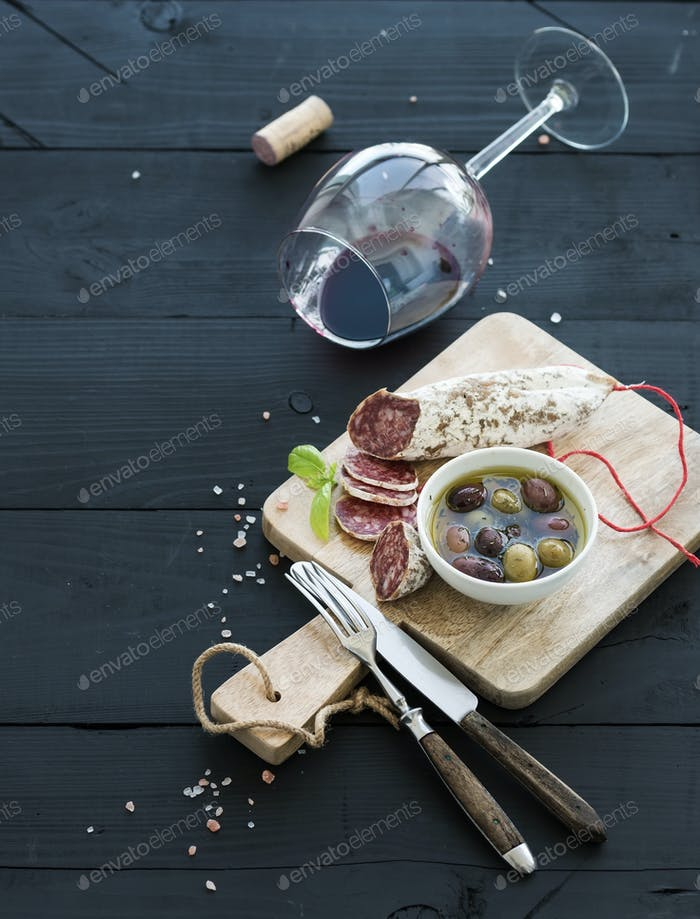 Wine appetizer set. Glass of red wine, French sausage and olives on black wooden backdrop