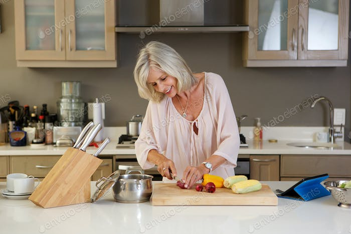 beautiful older woman in kitchen cutting healthy fresh vegetables