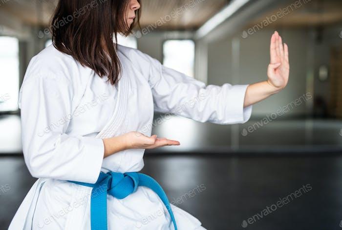 Una sección media de una mujer joven practicando karate en el gimnasio.