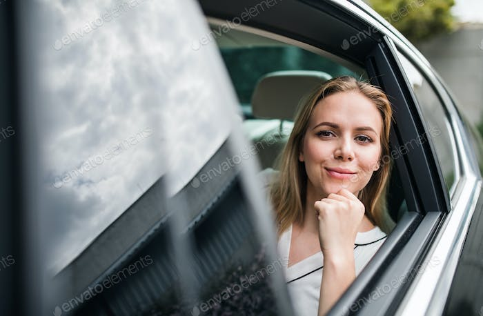 Business woman sitting on back seats in taxi car, looking out